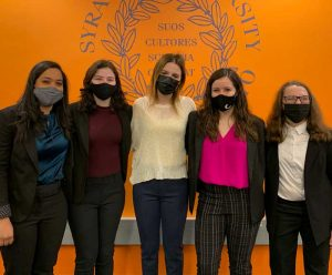5 women in masks are posed in front of the S.U. Seal