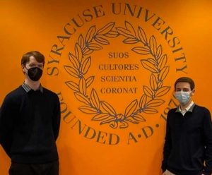 Two young men are posed next to the S.U. seal