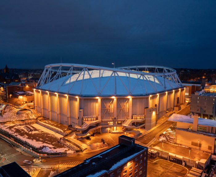 A nighttime photo of the stadium at Syracuse University with the City of Syracuse skyline in the background.