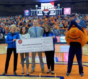 A large check is held between 4 people on a basketball court