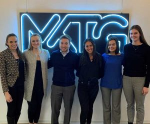 6 students are posed in front of a lit MKTG logo