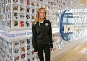 A female students stands in front of an NCAA office wall of logos