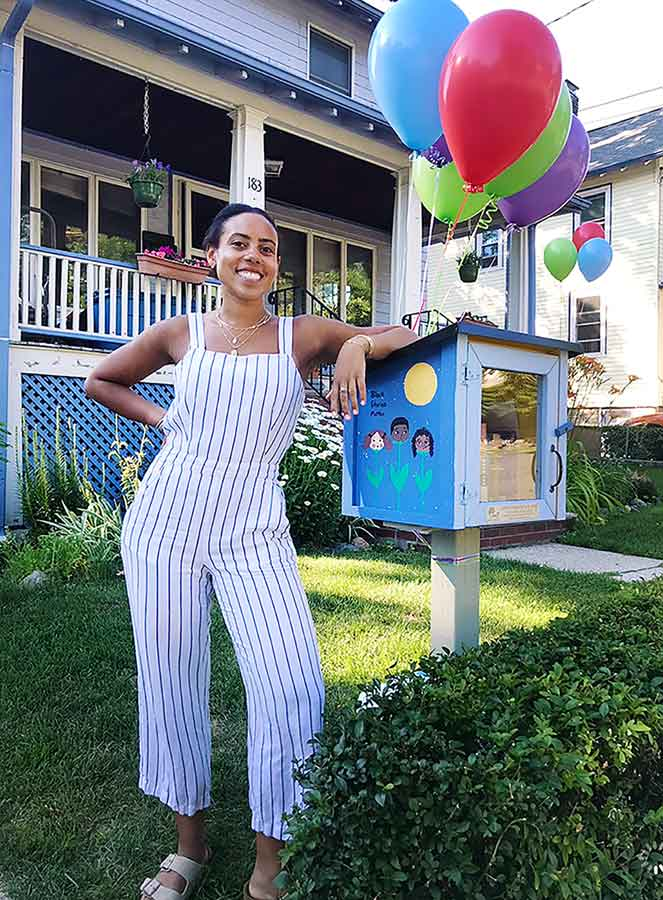 Kamya stands next to a small box in front of a house