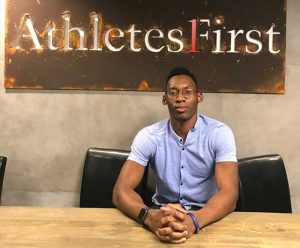Sean Onwualu sits in front of a sign saying Athletes First