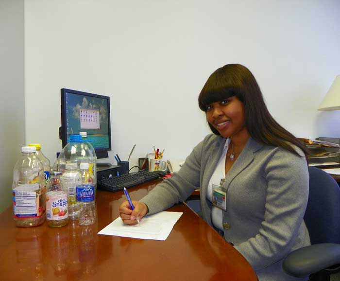 Shanique Campbell sits at research desk with various drink bottles
