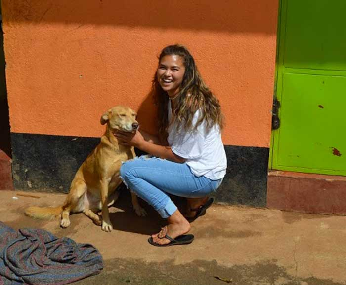 A girl is crouched next to a dog on a street
