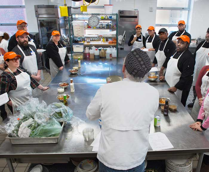 Overhead shot of Chef Bill Collins talks to a roundtable of students in a kitchen