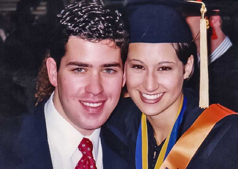 A couple is posed closely together in graduation clothing