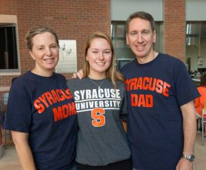 A student poses with her parents all are wearing Syracuse University shirts