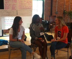 Three Syracuse University students seated in front of brainstorming materials talk with each other at the LIG Playmaker Retreat.