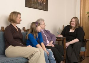 Therapy session with therapist and three clients.