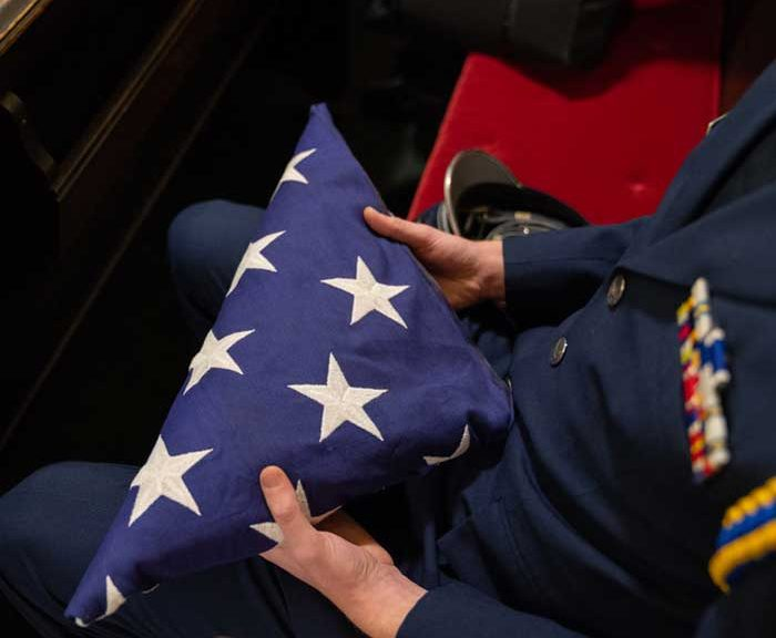 Decorated veteran holds a folded flag