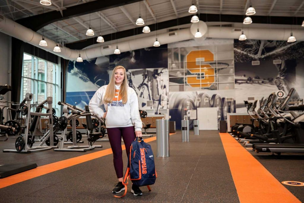 Student Alisamarie Yiatras standing in a gym area of the Barnes Center holding her backpack