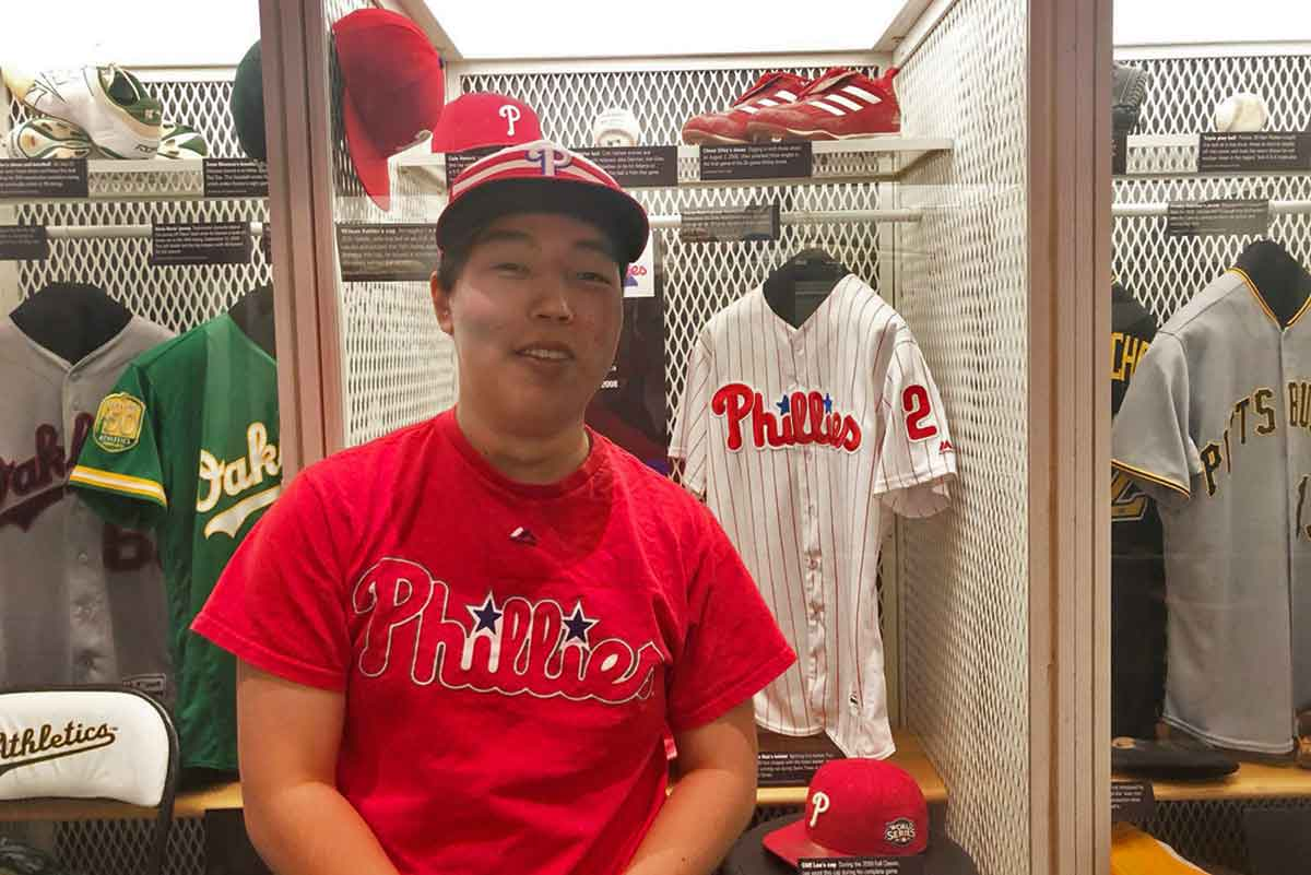 Person wearing Philadelphia Phillies fan apparel stands in front of a locker. Click to read the story.