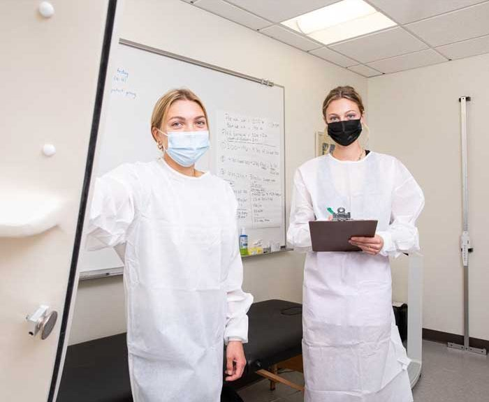 Two students standing wearing lab coats in a lab.