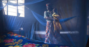 Tanzanian mother and baby in room with mosquito nets