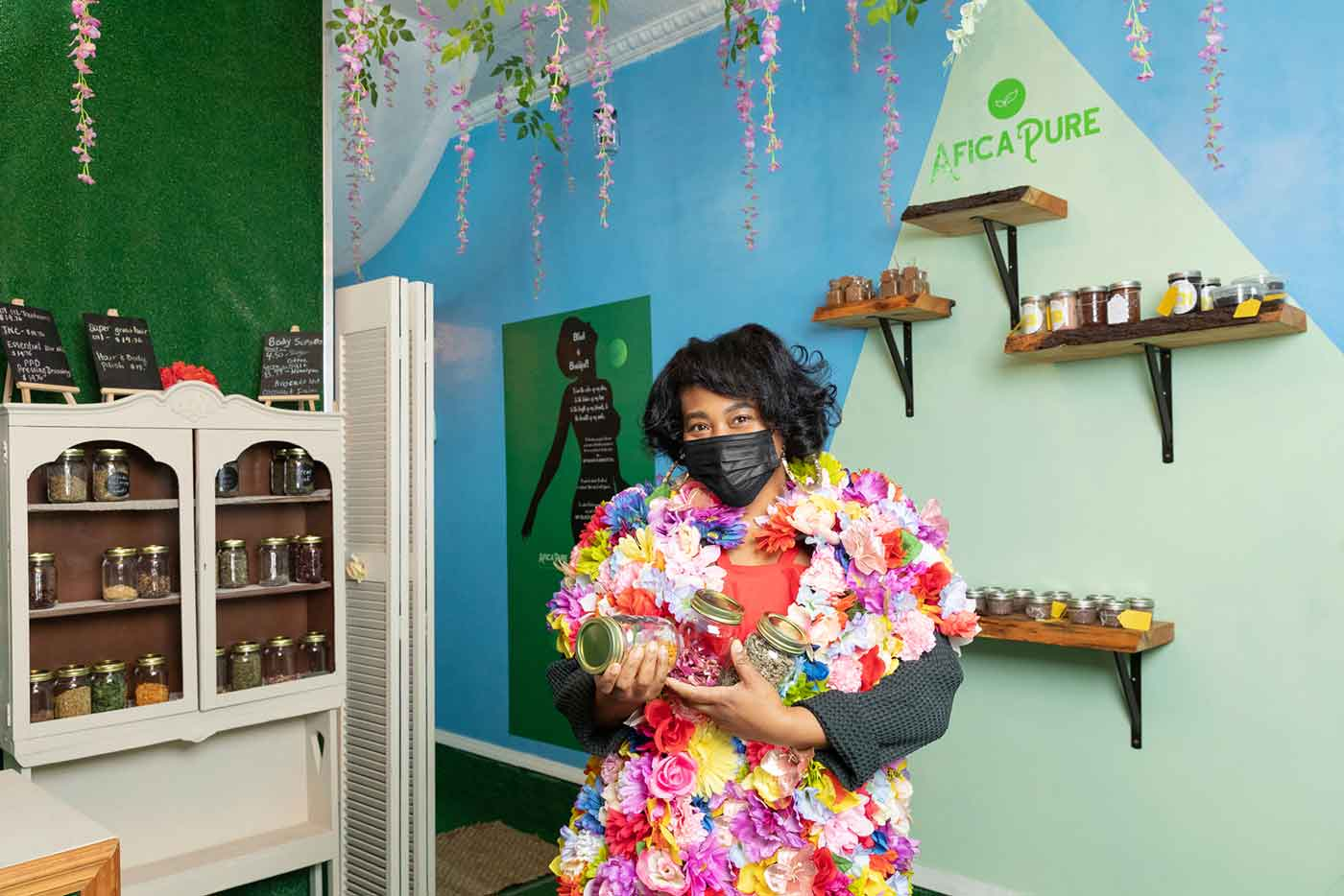 A women dressed in flowers holds jars of product