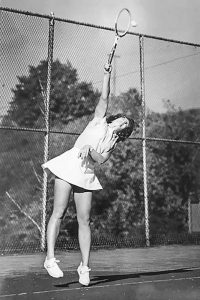 A women is jumping into the air to hit a tennis ball