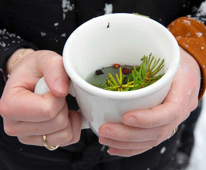 A close up of a person holding a mug of greens and water