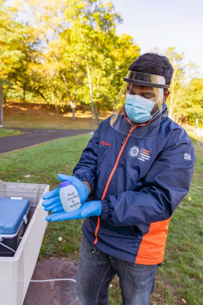 Person wearing mask, face shield and gloves shows the camera a water sample in a container.
