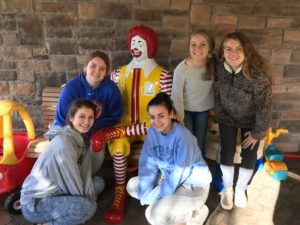 students pose with Ronald McDonald statue